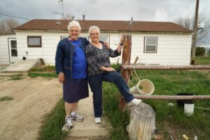 Ruth and Jane in front of a house made from a barrack that their family lived in.
