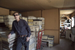 "Russ Rauchfuss in a former barracks building, used as a ""honey house"" for the family beekeeping business."