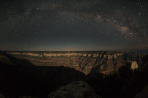 Milky Way arches over moonlit rim.