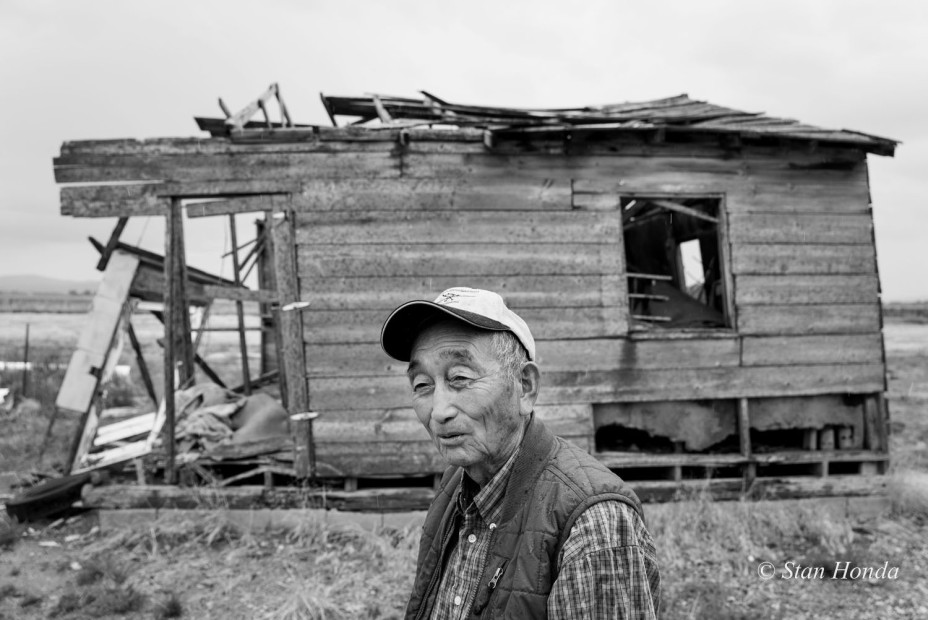 Farmer Tak Ogawa by a dilapidated barrack on his land. He came to the area after the original homesteaders had settled.