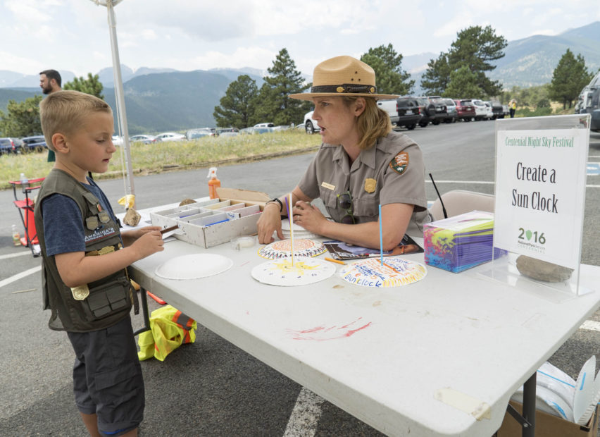 Ranger Cynthia Langguth helps a junior ranger with the sun clock.
